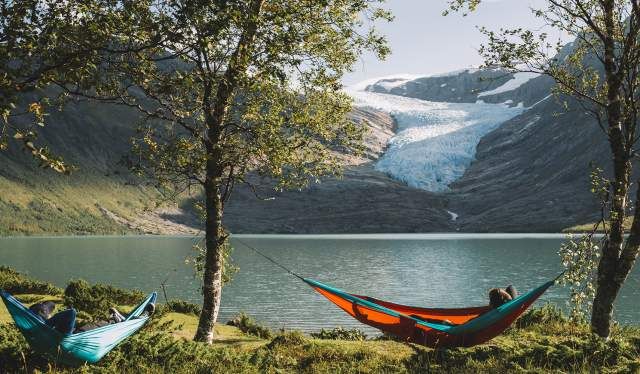 Folk i hengekøyer foran Svartisen på Helgeland i Nord-Norge