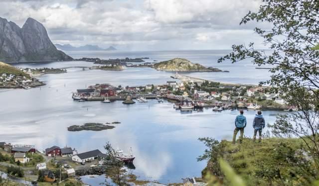 To mennesker ser utover Reine og fjorden og fjellene rundt
