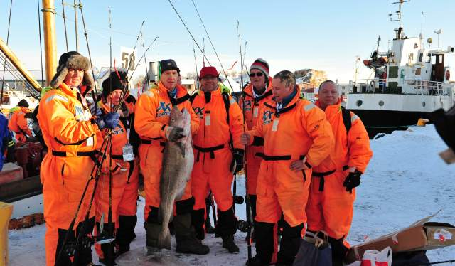 A fishing crew with an enormous cod, all participating in The world cod fishing championship in Lofoten, Northern Norway