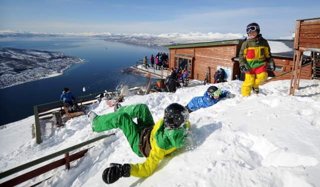 A group of kids playing in the snow at Narvikfjellet ski resort with a wide view of the sea below in Narvik, Northern Norway