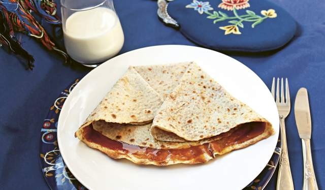 """Lefse with a brown cheese spread called """"møsbrøm"""" served on a platter and a glass of milk in Norway"""