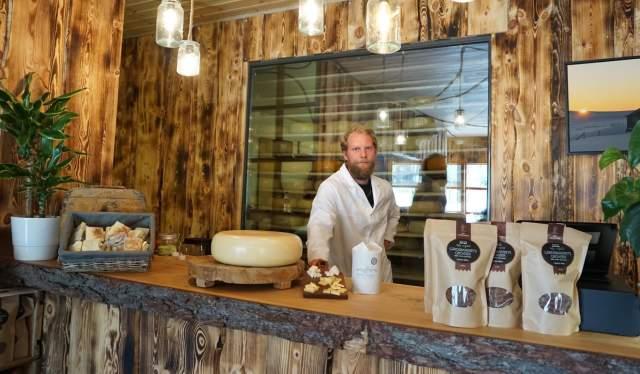 Een man die achter de toonbank staat in de kaasfabriek Hol Ysteri in Hallingdal, Oost-Noorwegen