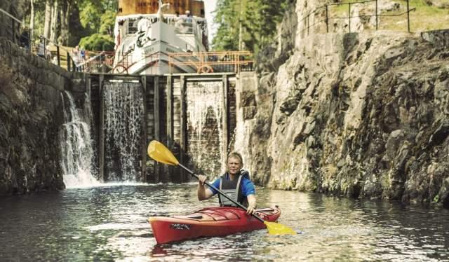 Een man aan het peddelen in een kajak op het Telemark-kanaal in Oost-Noorwegen