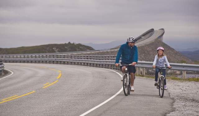 Father and daughter cycling on The Atlantic Road in the Northwest, Fjord Norway