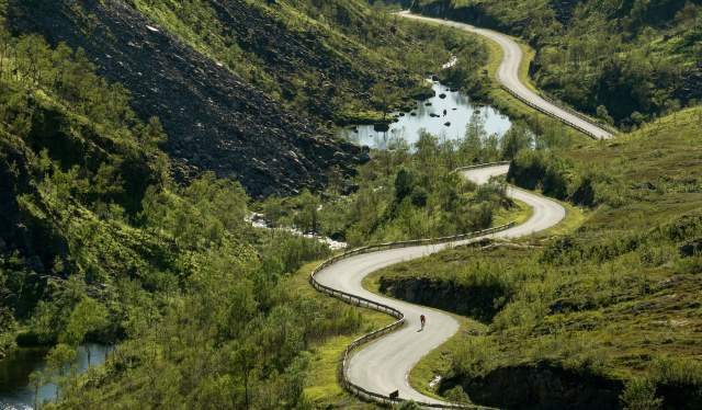A person road cycling through Kaperskaret at Senja in Northern Norway