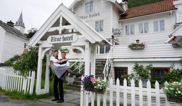 Bente R. and Kjetil Widding, owners of Utne Hotel, standing outside the hotel in the Hardangerfjord region in Fjord Norway