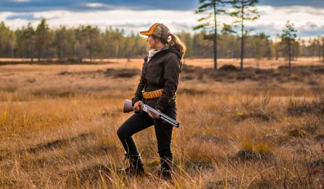 En kvinne jakter i skogen om høsten