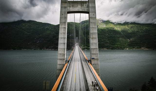 A group of road cyclists crossing a bridge in Fjord Norway