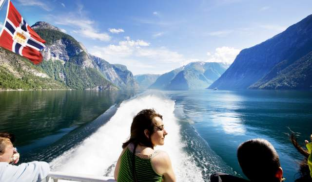 A group of people sitting at the bow of a boat going down Sognefjorden in Bergen, Fjord Norway. They're enjoying the view of the fjord and the surrounding mountains.
