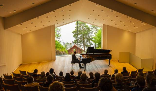 Man playing the piano in front of an audience at the Troldsalen room at Edvard Grieg Museum Troldhaugen in Bergen, Norway