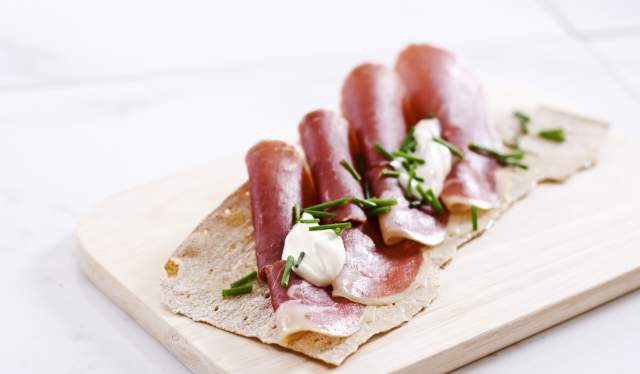 Norwegian flatbrød (flat-bread) served with sliced, smoked ham served on a wooden platter in Norway