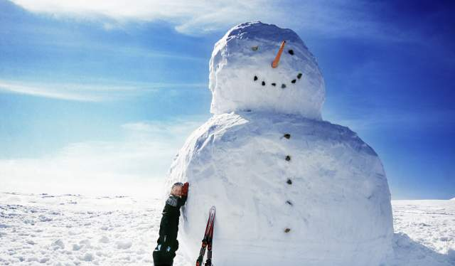 A boy and a gigantic snowman in Trysil, Eastern Norway