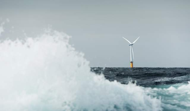 Floating offshore wind turbine, with a large wave in the foreground
