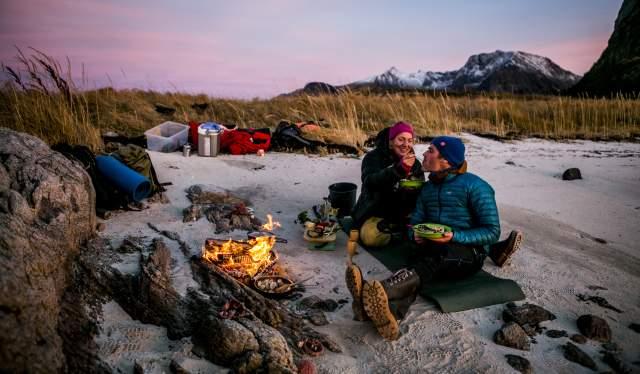 Et par spiser middag ved bålet på stranden i Steigen i Nordland, Nord-Norge