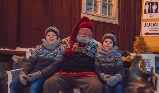 Two children sitting next to Santa Claus at Røros Christmas Market in Trøndelag, Norway