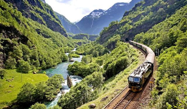 The Flåm railway going through the landscape of green hills and spectacular mountains in the background in Bergen, Fjord Norway.