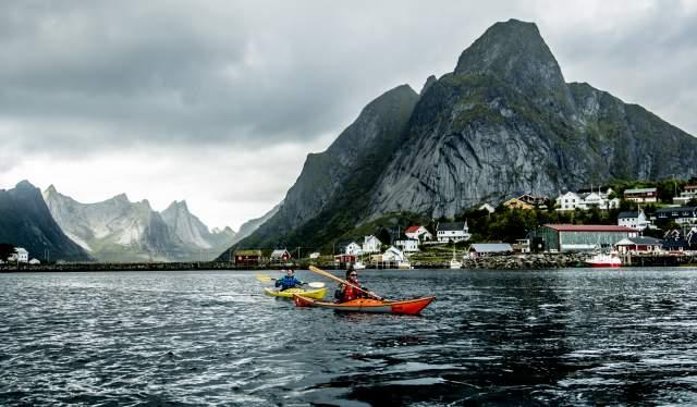 To personer er ute og padler i kajakk i Reine, Lofoten