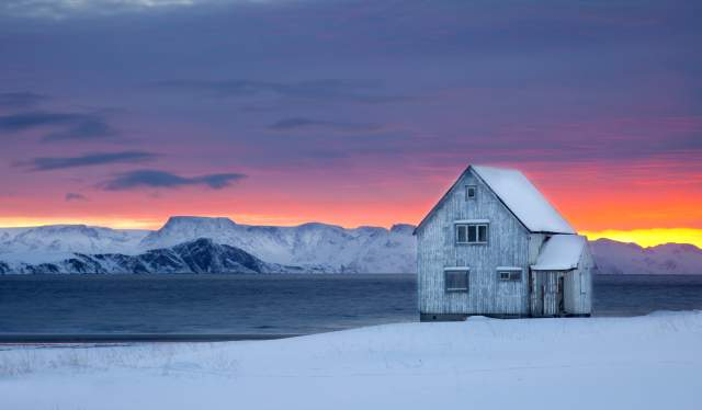 A wooden house next to the water on a snow-covered landscape with sunset colors in the background at Hasvik in Finnmark, Northern Norway