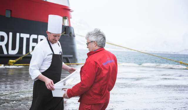 A chef in front of a Hurtigruten ship takes a tray with fresh fish, Northern Norway
