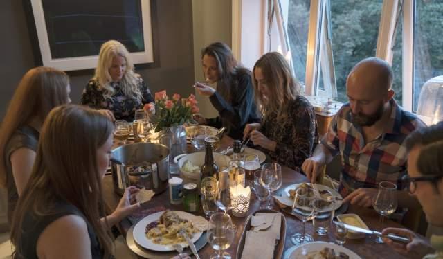 Folk rundt et middagsbord der det serveres fårikål, i Oslo på Østlandet