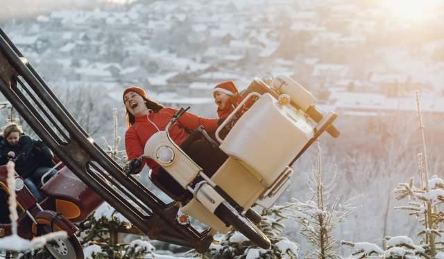 Mor og barn kjører karusell nissedrakter i Kongeparken utenfor Stavanger på Vestlandet