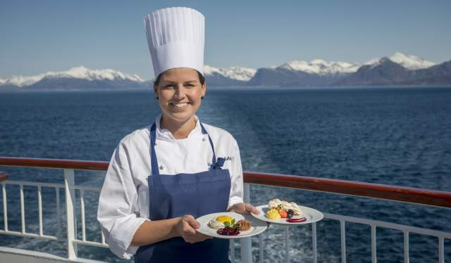 A female chef standing on the deck of a Hurtigruten ship with two plates of food