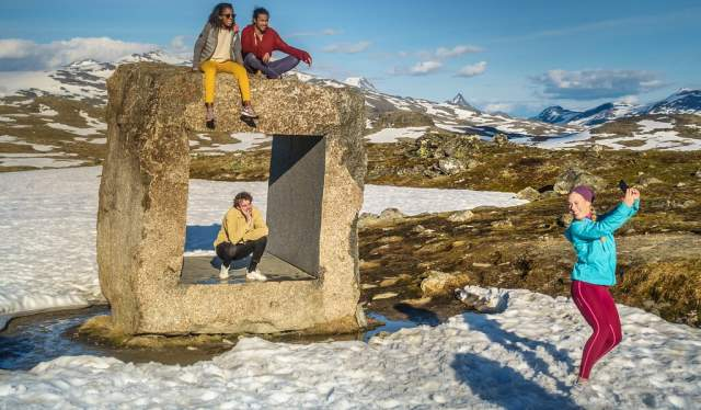 Four friends on an art installation on Norwegian Scenic Route Sognefjellet in Fjord Norway