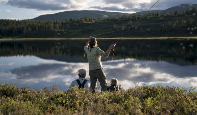 En kvinna och hennes familj är ute på flugfiske i en insjö i Blefjell i regionen Østlandet (östra Norge)