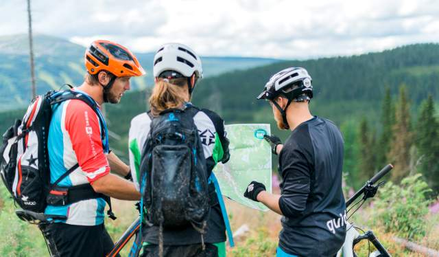 Mountain bikers planning a trail cycling trip in Trysil, Eastern Norway, with a guide