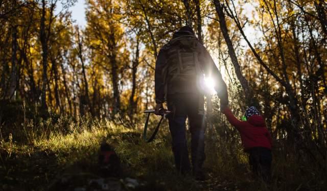 En far holder sin sønn i hånden mens de går gjennom skogen med høstsolen skinnende inn mellom grenene