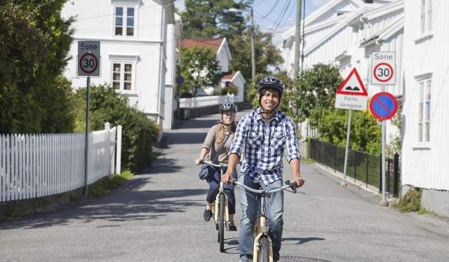 Two people cycling on a road in Grimstad, Southern Norway