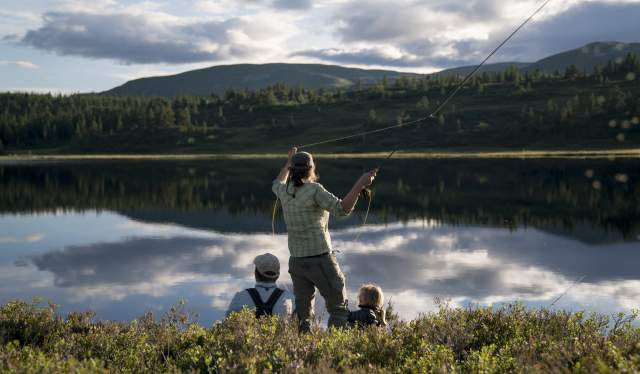A woman and her family is fly-fishing in a lake in Blefjell, Eastern Norway