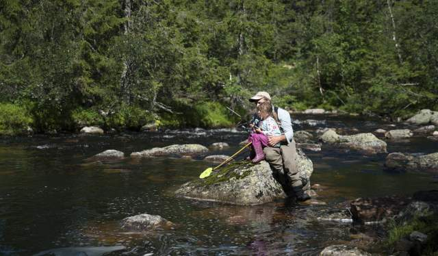 A father helps his daughter to fish in a river in Blefjell, Eastern Norway