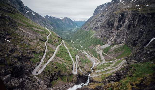 """The curvy road up the steep mountain called """"Trollstigen"""" in Geiranger in fjord Norway"""