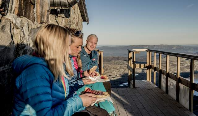 Three people eating waffles at Gaustatoppen mountain cabin in Telemark, Norway
