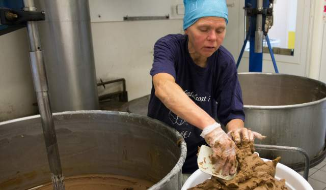 Woman making brown cheese at the cheese factory Undredal Stølsysteri in Aurland in the Sognefjord region of Fjord Norway