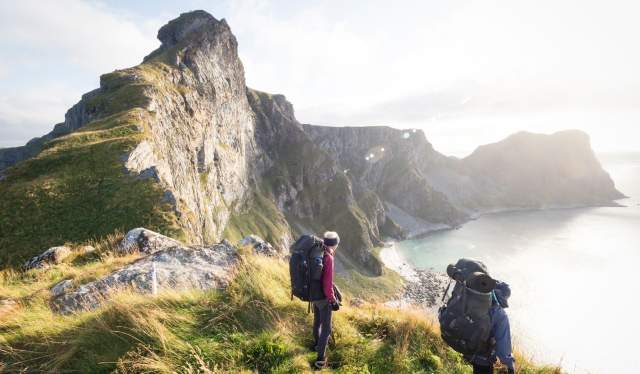 Two people hiking on the mountain of Værøy island in Lofoten in Northern Norway