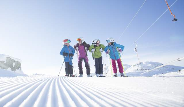 Four kids with skiers stand on a freshly groomed slope next to a button lift in Hemsedal, Eastern Norway