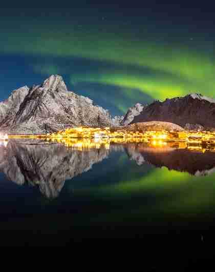 Vista de las auroras boreales sobre el pequeño pueblo de pescadores de Reine, en Lofoten, Norte de Noruega.