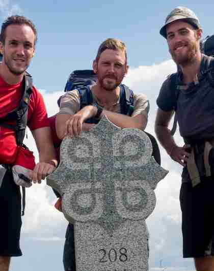 Three men standing around a milestone on the pilgrimage path to Trondheim, Norway