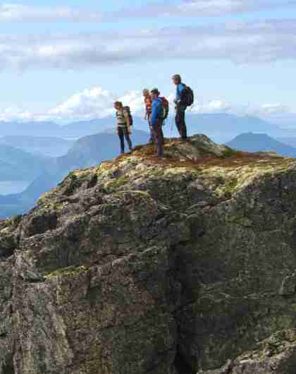 A group of people admire the view from Romsdalseggen in Fjord Norway