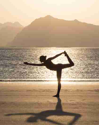A women practicing yoga in silence on the beach in Lofoten, Northern Norway