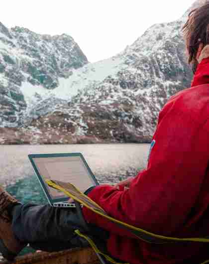 A man working outdoors by the sea at the Arctic Coworking Lodge in Lofoten, Northern Noway
