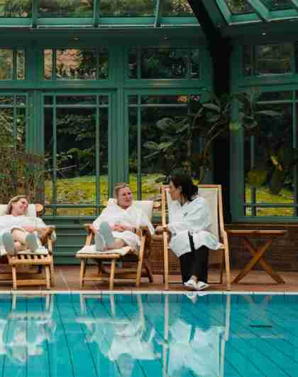 Fire damer slapper av ved bassenget inne på Engø gård på Tjøme, Østlandet