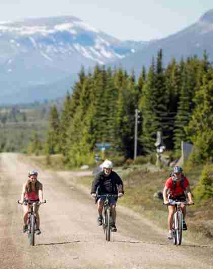 Three people cycling on a gravel road with mountains in the distance