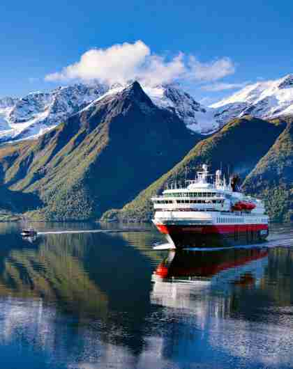 A Hurtigruten ship on the Hjørundfjord in Fjord Norway surrounded by snow-clad mountains