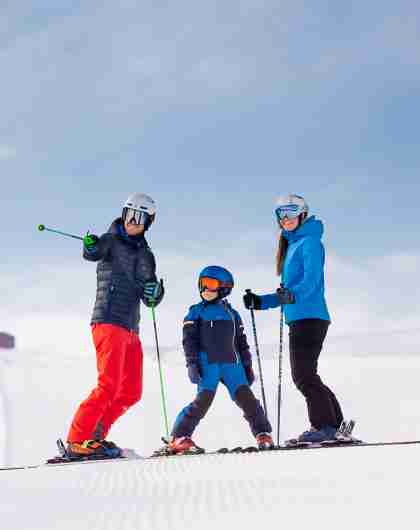 A family of three is skiing in the slopes of Trysilfjellet mountain in Trysil, Eastern Norway.