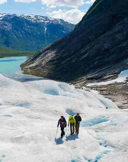 Three people hiking on the Nigardsbreen glacier in Fjord Norway