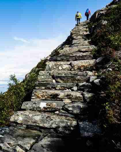 To mennesker klatrer opp steintrappa Midsundtrappene mot Rørsethornet nær Molde på Vestlandet