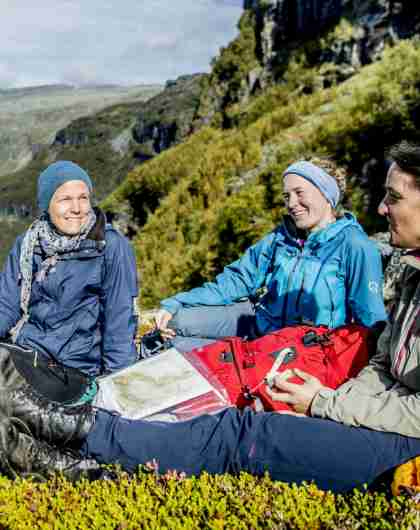 Plan your trip to Norway. People with maps resting in the Aurlandsdalen valley